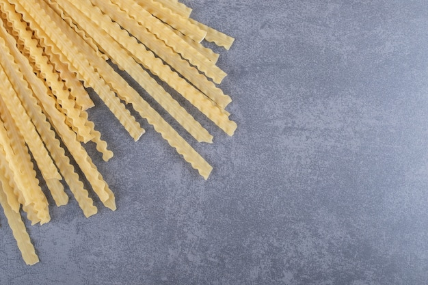 Stelletje verschillende-vormige droge pasta op stenen achtergrond.