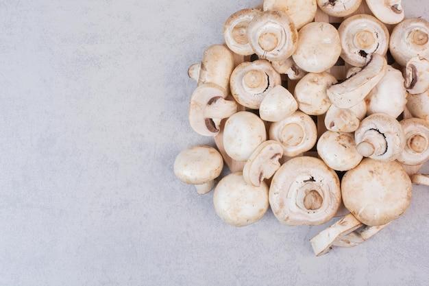 Stelletje verse champignons op marmeren tafel.