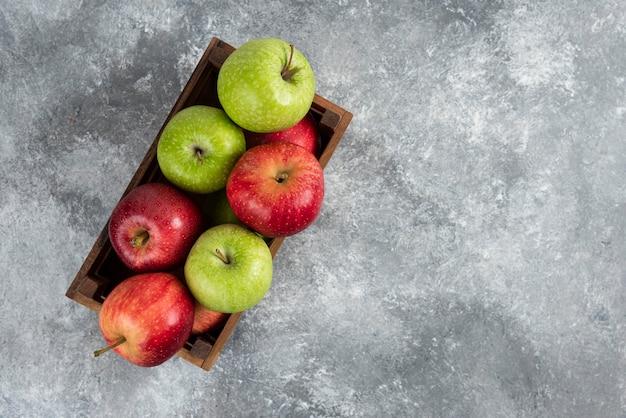 Stelletje verse groene en rode appels geplaatst in houten kist.