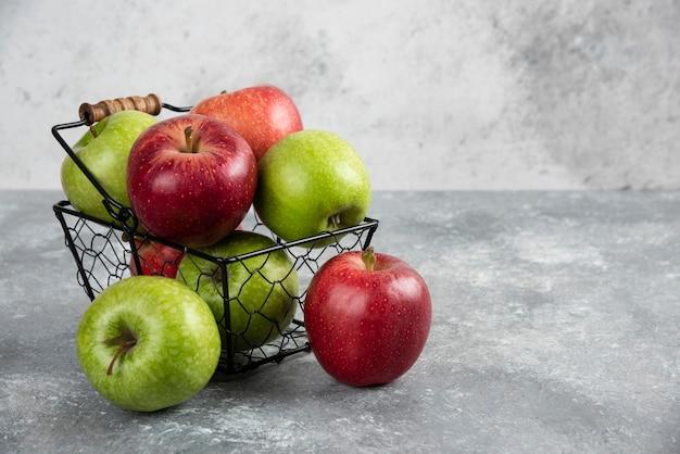 Stelletje verse groene en rode appels geplaatst in metalen mand.
