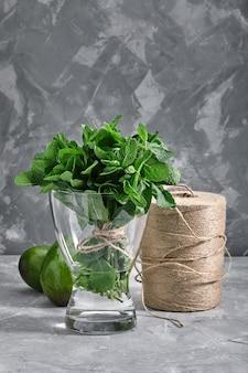 Stelletje verse munt in een vaas met water op een grijze achtergrond. het concept van vers voedsel, verpakking en online levering van producten. kopieën van de ruimte.