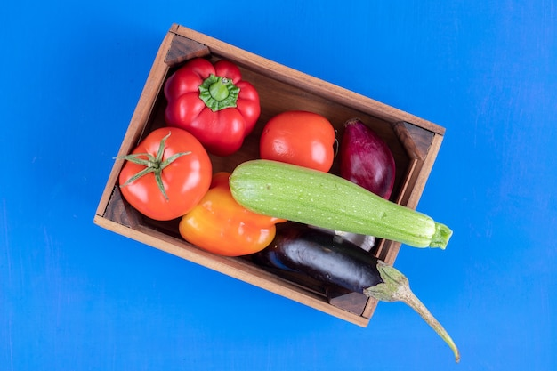 Stelletje verse rijpe groenten in houten kist op blauwe ondergrond.