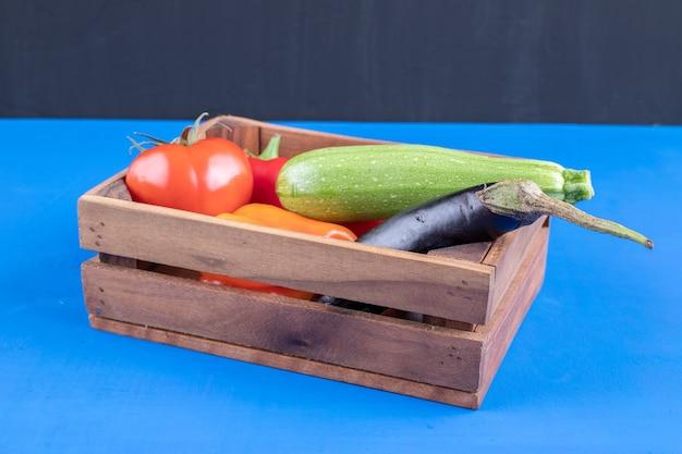 Stelletje verse rijpe groenten in houten kist op blauwe ondergrond