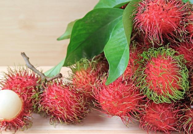 Stelletje verse rijpe rambutan hele vruchten en geopend om verrukkelijk sappig wit vlees te laten zien