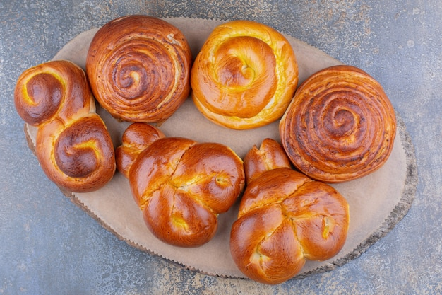 Stelletje zoete broodjes op een houten bord op marmeren oppervlak
