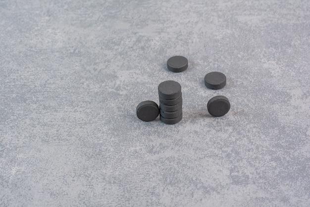 Stelletje zwarte pillen op marmeren tafel.
