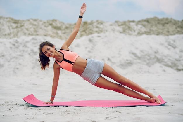 Stelt de geschiktheids mooie vrouw die haar lichaamskernspieren met yoga opleiden