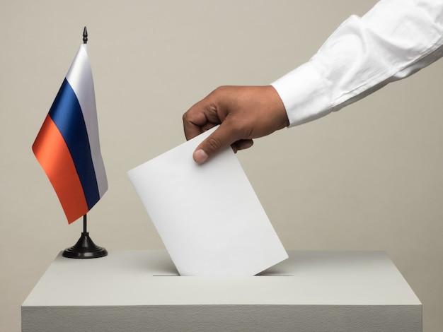 Stembus met nationale vlag van rusland. presidentsverkiezingen in 2018. hand gooien van een stembiljet