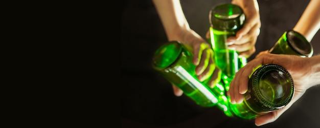 Stemming. handen van vrienden, collega's tijdens bier drinken, plezier maken, rammelende flessen, glazen samen.