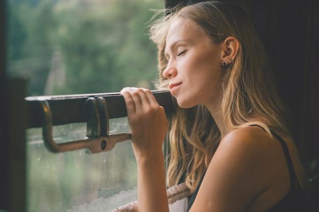 Stemming sfeervol levensstijlportret van jonge mooie blonde haarvrouw die in venster van het berijden van trein ademen.