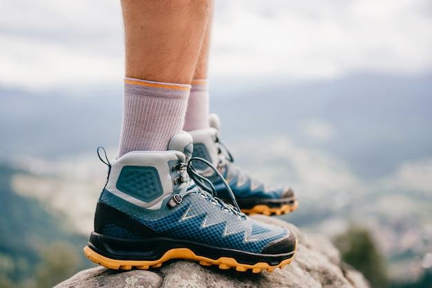 Stemmingsfoto van mannelijke benen die sportieve wandelschoenen dragen met sterke beschermende zool. de benen van mensen in trekkingsschoeisel voor bergreis die zich op steen openlucht bij aard bevinden