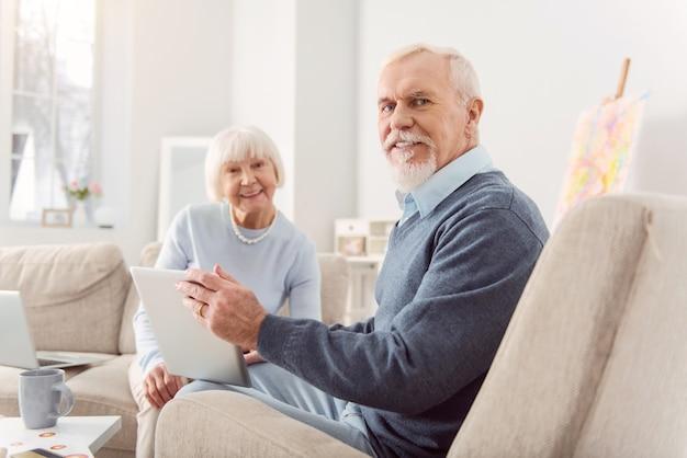 Stemmingsverhogende boodschap. vrolijke oudere man en zijn geliefde vrouw zitten in de woonkamer en kijken naar een videoboodschap van hun kinderen op tablet