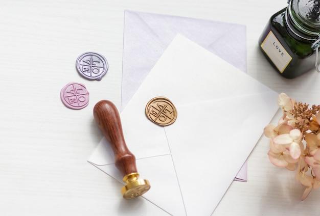 Stempel en envelop op een witte tafel, bovenaanzicht