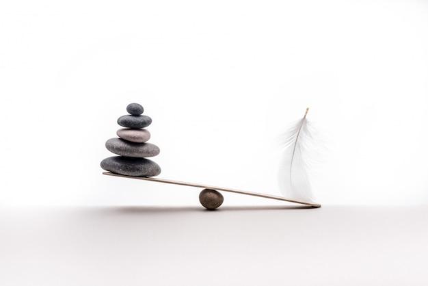 Stenen balans met pluim. concept van zwaar en licht.