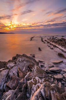 Stenen bij zonsondergang van het geopark genaamd flysch op het strand van sakoneta in de stad deba, aan de westkant van het geopark van de baskische kust, guipúzcoa. baskenland. verticale foto