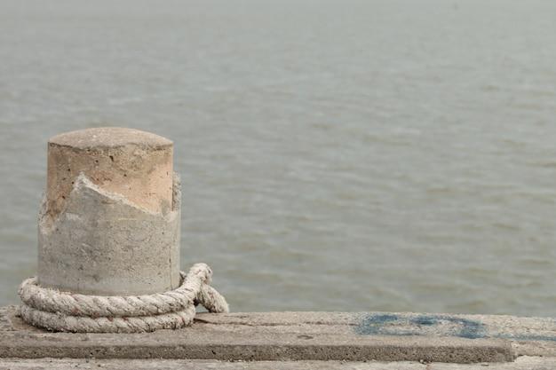 Stenen bolder met touw op boot dok en zee