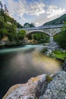 Stenen brug, kleurrijke rivier en wolken