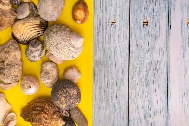 Stenen en schelpen op een blauwe houten achtergrond en een gele achtergrond.marine thema