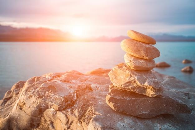 Stenen gestapeld in de zee bij zonsondergang