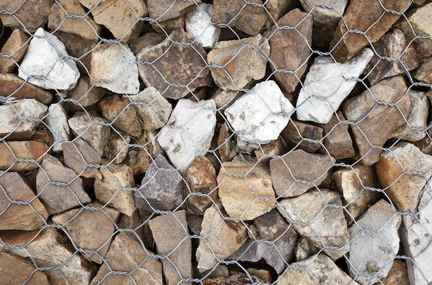 Stenen in schanskorf, draadmetaal gedraaid gaas met stenen, een element van landschapsontwerp.