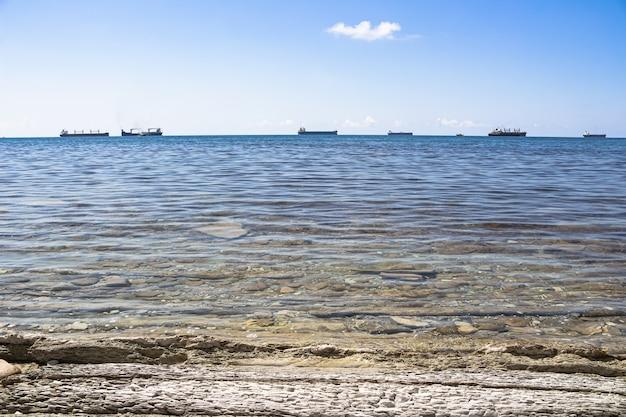 Stenen kust met uitzicht op de heldere en transparante zee en vrachtschepen op een heldere zonnige dag