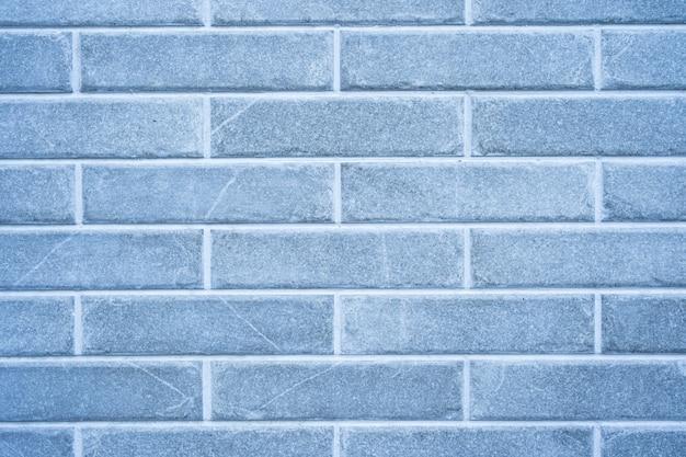 Stenen muur. het patroon van grijze baksteen met witte vulling