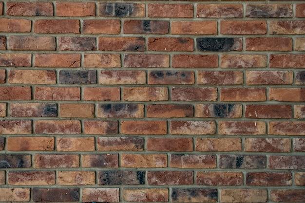 Stenen muur. het patroon van rode baksteen met grijze vulling