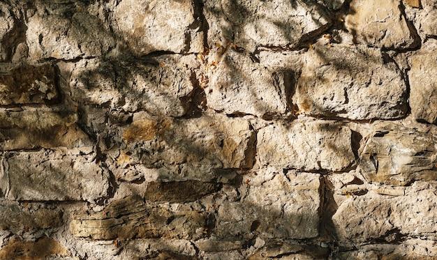 Stenen muur, oude afbrokkelende stenen muur gemaakt van steen en zandsteen, abstracte aard achtergrond
