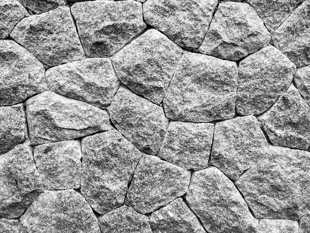 Stenen muur textuur achtergrond. abstracte oppervlak van donkere sterke grijze rotswand verschillende vorm.