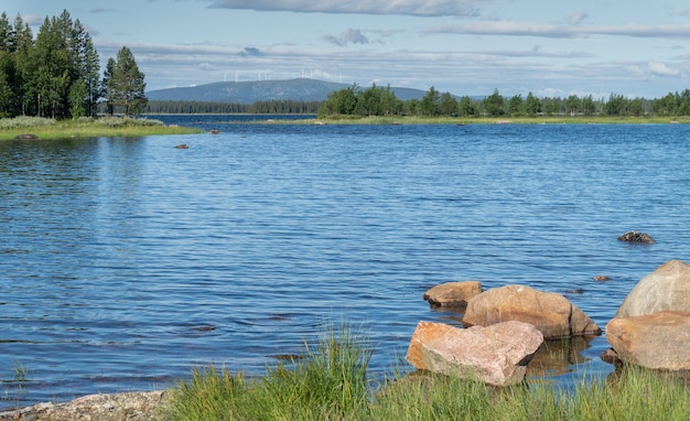 Stenen op een blauw meer tegen de achtergrond van een groen bos, zweden