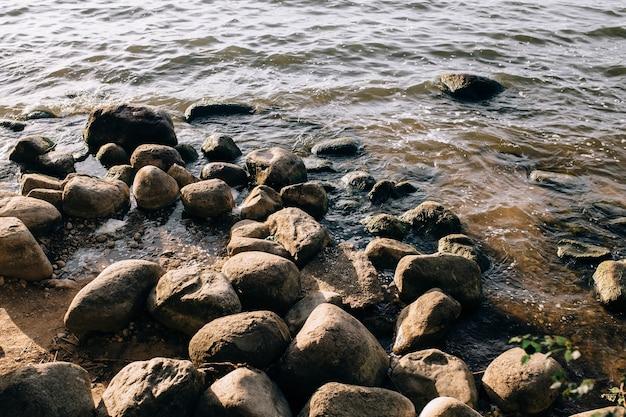 Stenen op het meer in de mist. grote en kleine stenen. het water is transparant en onder water zie je stenen die begroeid zijn met slib. ruimte kopiëren.