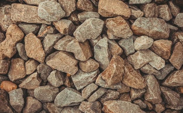 Stenen pad achtergrond hierboven. sluit het behang. veel stenen. de stenen zijn klein en groot. verschillende maten en kleuren stenen. grind