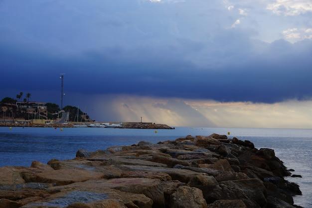 Stenen pier, kijkend naar zee, de zonnestralen banen zich een weg door de onweerswolken