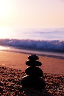 Stenen piramide op het strand bij zonsondergang