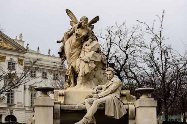 Stenen sculptuur in wenen van een fee bovenop een persoon zittend op een bankje.