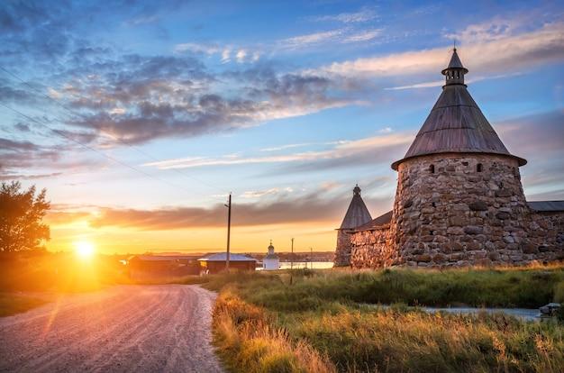 Stenen torens van het solovetsky-klooster in het licht van de ondergaande zon en de weg