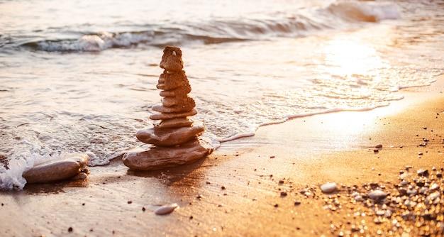 Stenen van de piramide op het strand symboliseren het concept van zen, harmonie, balans.