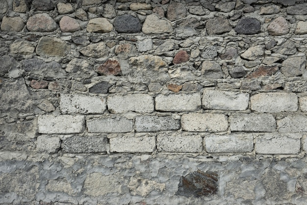 Stenen van verschillende afmetingen en vormen liggen op elkaar. cement tussen hen. t