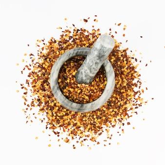 Stenen vijzel en stamper vol gemalen rode cayennepeper, gedroogde chili vlokken en zaden geïsoleerd op een witte. zelfgemaakte kruideningrediënten om te koken.