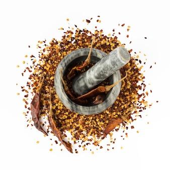 Stenen vijzel en stamper vol gemalen rode cayennepeper, gedroogde chili vlokken en zaden geïsoleerd op een witte