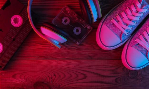 Stereohoofdtelefoons, audio- en videocassette, sneakers op houten oppervlak. neon rood en blauw licht