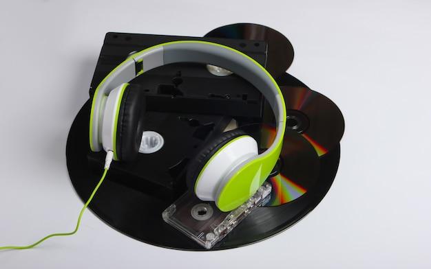 Stereohoofdtelefoons, videocassettes, vinylplaten, audiocassette, cd-schijven op een wit oppervlak