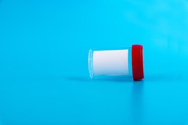 Steriele transparante lege plastic container voor analyse. rood deksel. steriele medische container voor biomateriaal. geïsoleerd op een blauwe achtergrond.