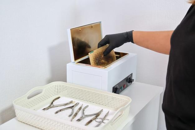Sterilisatie van manicure-instrumenten met droge hete lucht in een autoclaaf, desinfectie van bacteriële en virale infecties. handen van manicure in handschoenen met tools