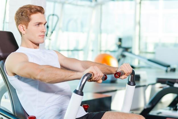 Sterk en gezond blijven. knappe jonge man die geconcentreerd kijkt tijdens het sporten in de sportschool