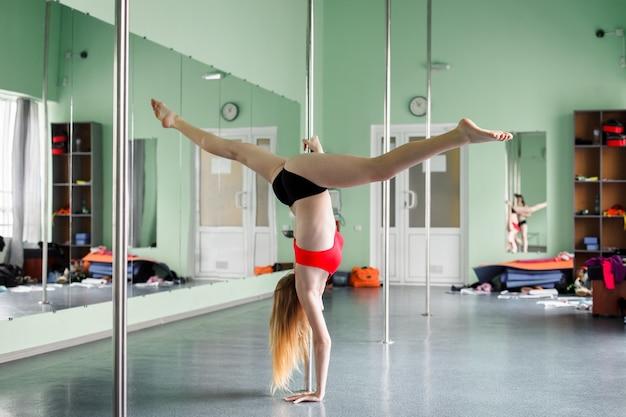 Sterk en gracieus meisje danst op een paal.