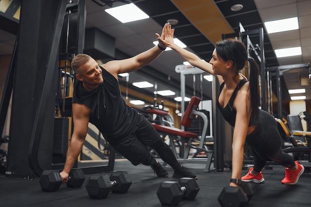Sterk en mooi atletisch fitnesspaar in trainingskleren die push-up oefeningen doen en elkaar een high five geven