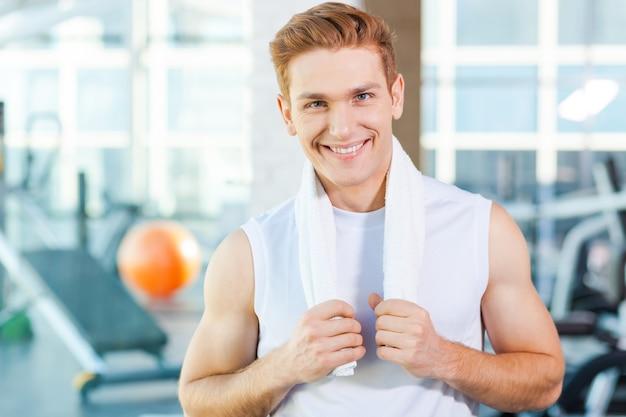 Sterk en zelfverzekerd. zelfverzekerde jonge gespierde man die een handdoek op de schouders draagt en glimlacht terwijl hij in de sportschool staat