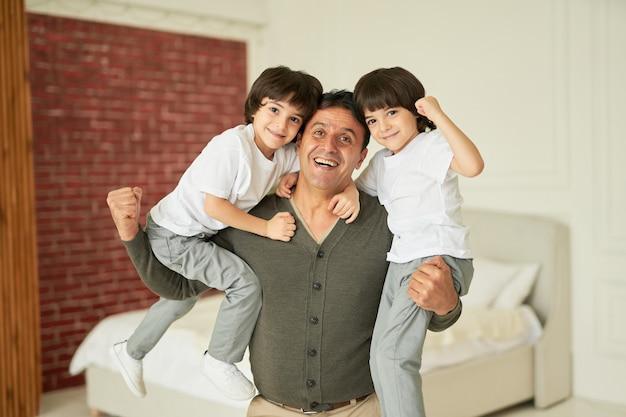 Sterk jongensportret van een vrolijke latijnse familie die van vader houdt en kleine tweelingjongens vasthoudt en glimlacht