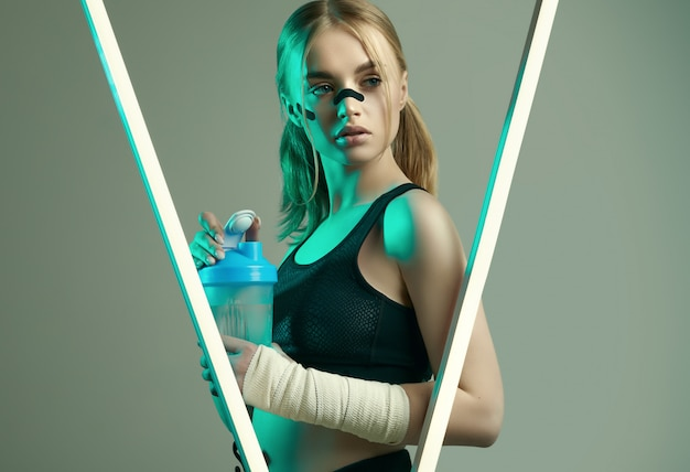 Sterk mooi meisje met blond haar, sportfiguur, zelfverzekerde blik, vuisten in beschermende boksbanden